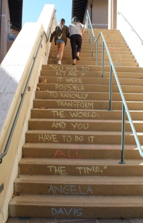 "Students climb stairs chalked with an Angela Davis quote: ""You have to act as if it were possible to radically transform the world and you have to do it all the time."" Photo by Casey Chaffin"